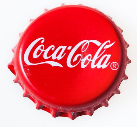 Moscú, Rusia - 12 diciembre 2105: Vista superior de la tapa roja usada de la botella de vidrio de Coca-Cola. The Coca-Cola Company es una empresa de bebidas y fabricante estadounidense fundada en 1886.