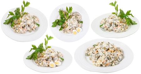 ensalada rusa: juego de placas con Olivier ensalada rusa con mayonesa aislado en fondo blanco