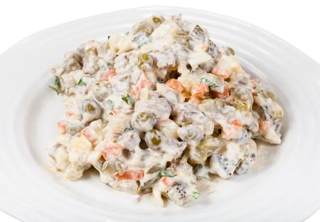 russian salad: Olivier ensalada rusa con mayonesa en la placa aislada en el fondo blanco