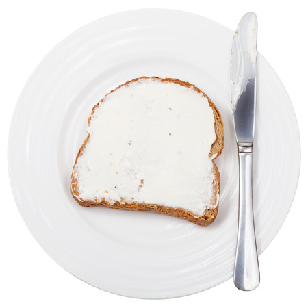 sandwich spread: top view of grain bread and Cheese spread sandwich with table knife on white plate isolated on white background