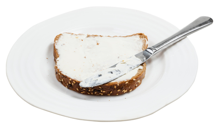 sandwich spread: grain bread and Cheese spread sandwich with table knife on white plate isolated on white background