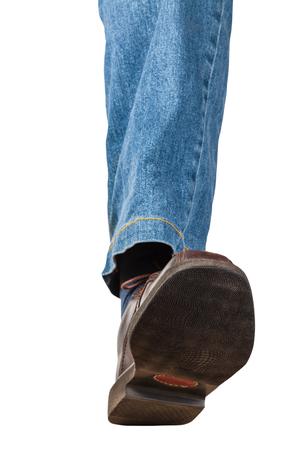 vue de face de la jambe gauche mâle en jeans et chaussures marron fait un pas isolé sur fond blanc Banque d'images