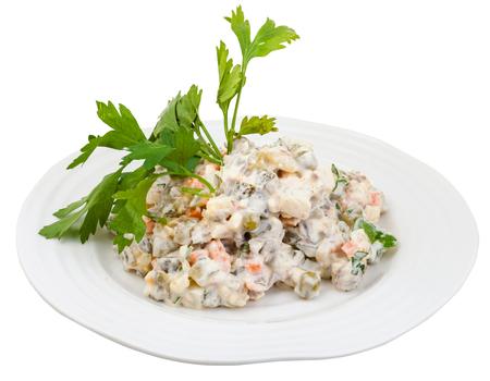 ensalada rusa: Olivier ensalada rusa con mayonesa decorado con perejil verde en un plato blanco aisladas sobre fondo blanco