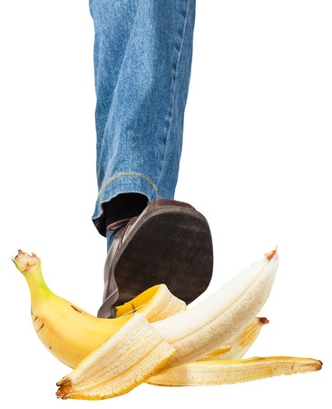 stepping: male left leg in jeans and brown shoe stepping on banana isolated on white background