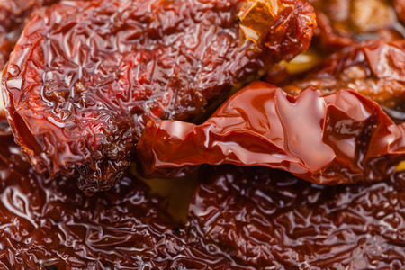sundried: food background - few sun-dried red tomatoes in olive oil