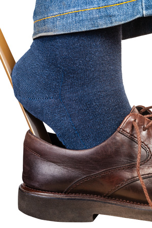 levis: man puts on brown shoes using shoe horn close up isolated on white background