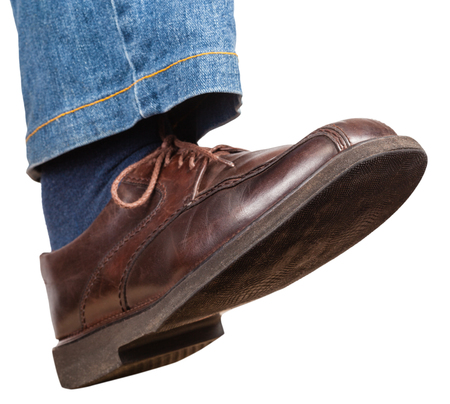 stride: step of male right leg in jeans and brown shoe isolated on white background