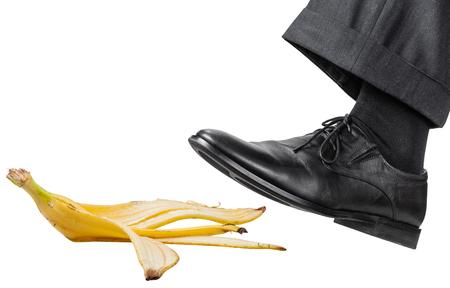 pie masculino en el zapato negro izquierda se desliza sobre una cáscara de plátano aislados sobre fondo blanco
