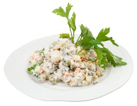 ensalada rusa: Olivier ensalada rusa con mayonesa decorado con verduras frescas en un plato blanco aisladas sobre fondo blanco