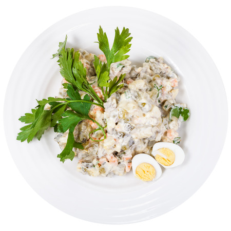 ensaladilla rusa: top view of olivier russian salad with mayonnaise decorated with green parsley and boiled eggs on white plate isolated on white background