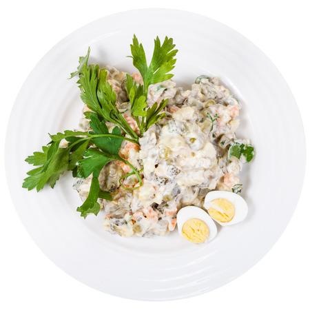 russian salad: vista desde arriba de ensalada rusa con mayonesa olivier decorado con perejil verde y huevos cocidos en un plato blanco aislado en el fondo blanco Foto de archivo