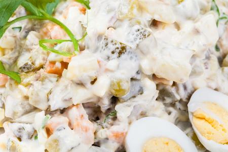ensaladilla rusa: Olivier ensalada rusa con mayonesa de cerca decorado con perejil verde y huevos cocidos Foto de archivo