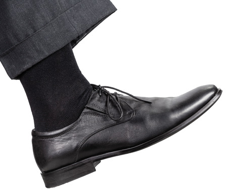 stride: side view of male right leg in black shoe takes a step isolated on white background