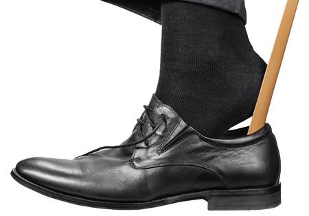 hombre pone en el zapato negro con calzador aislado en fondo blanco Foto de archivo
