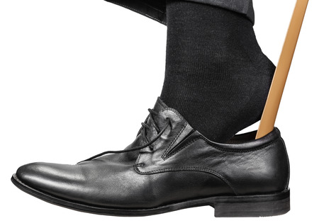 man puts on black shoe with shoehorn isolated on white background
