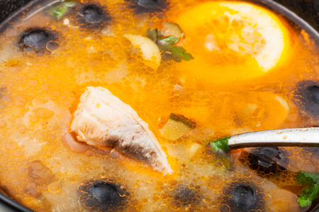 solyanka: surface of Solyanka russian traditional spicy and sour soup with fish in bowl close up