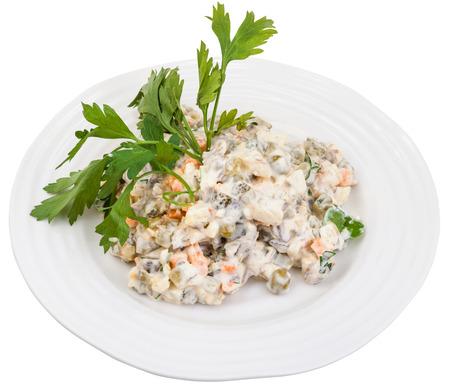 ensalada rusa: por encima de vista de ensalada rusa con mayonesa olivier decorado con perejil verde en plato blanco sobre fondo blanco Foto de archivo
