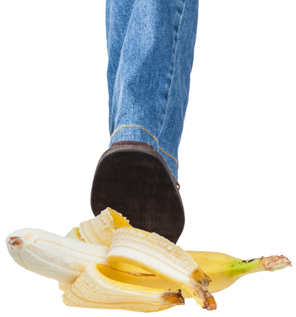 stepping: male left foot in jeans and brown shoe stepping on banana isolated on white background