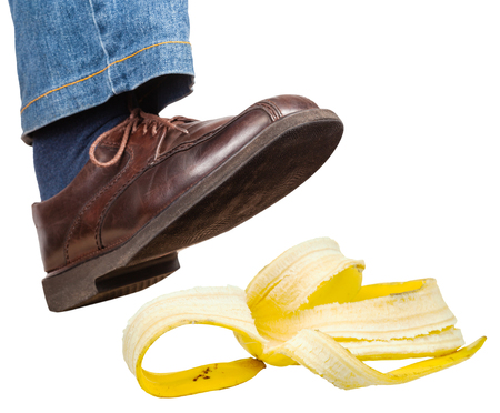 men s feet: male right foot in jeans and brown shoe slips on a banana peel isolated on white background