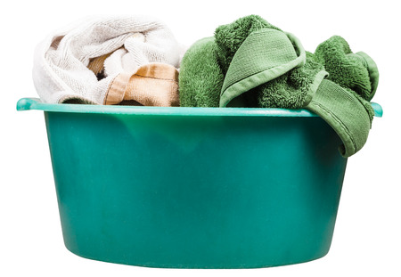 green clothes: side view of round green plastic wash basin with towels isolated on white background Stock Photo