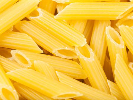 semolina pasta: food background - durum wheat semolina pasta penne rigate close up