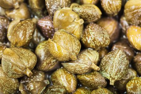 alcaparras: fondo del alimento - pila de alcaparras en vinagre verdes