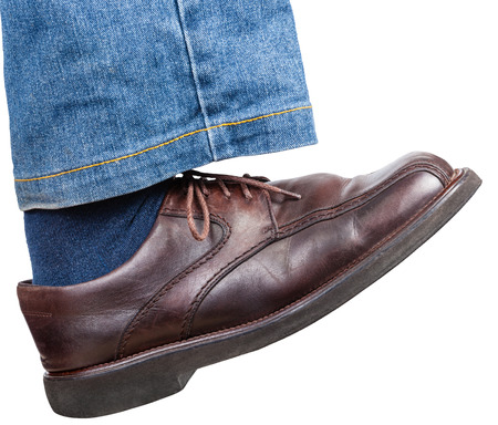 stride: side view of male right foot in jeans and brown shoe takes a step isolated on white background