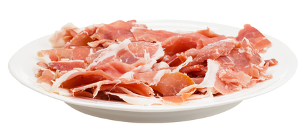 side plate: side view of thin sliced dry-cured ham on white plate isolated on white background