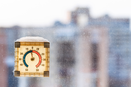 negative area: first frost in city - negative temperature on outdoor thermometer in cold weather Stock Photo