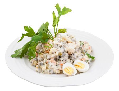 ensalada rusa: Olivier ensalada rusa con mayonesa decorado con perejil verde y huevos cocidos en un plato blanco aisladas sobre fondo blanco Foto de archivo