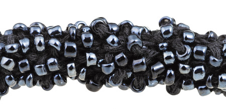 sewn up: beadwork - many black glass beads sewn on necklace close up isolated on white background Stock Photo