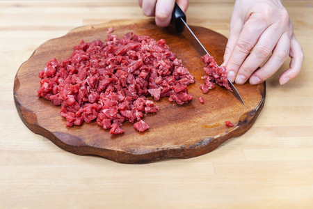 mujeres cocinando: woman finely chops meat on wooden cutting board on table
