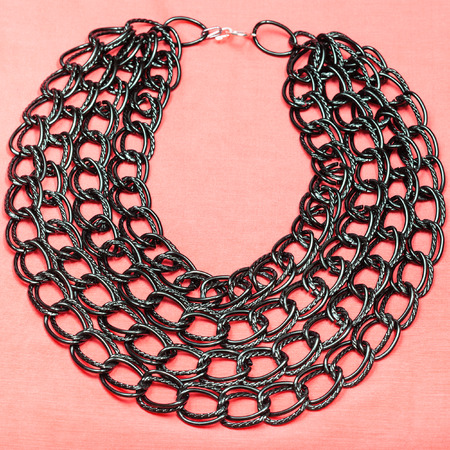 rosa negra: top view of necklace from strings of black chain on pink textile background
