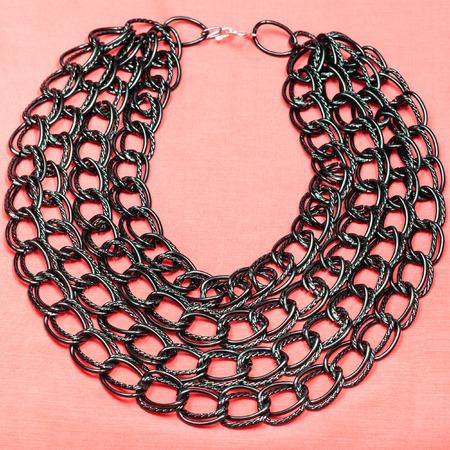 rosa negra: vista desde arriba del collar de las cadenas de la cadena negro sobre fondo de textiles de color rosa