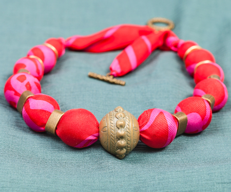red green: textile necklace from red silk and bronze beads on green background