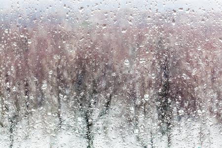 gocce d'acqua da sciogliere la neve sul vetro della finestra di casa in inverno