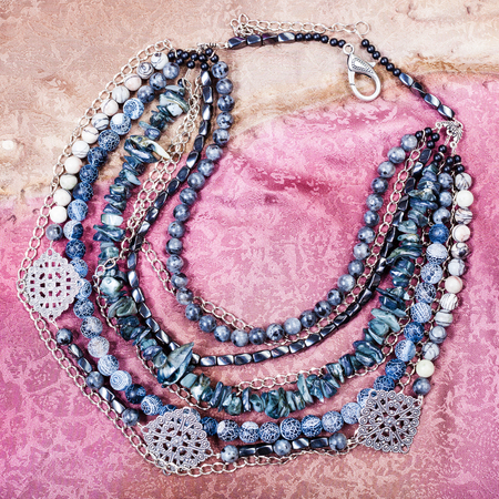 labradorite: top view of gray blue agate necklace from natural gemstones (Dragon Veins Agate, shell, silk jasper, hematite, labradorite beads) on painted textile background
