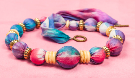 silk background: textile necklace from pink and blue painted silk balls and brass and bone rings on pink background