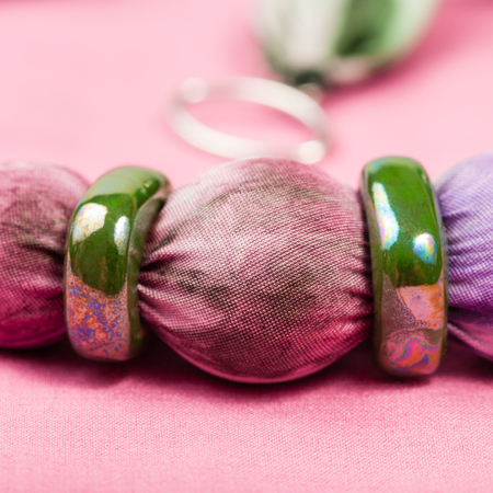 green background pattern: detail of handmade textile necklace - violet painted silk batik bead and green ceramic rings close up on pink background