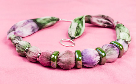 ornamental background: textile necklace from violet painted silk balls and green ceramic rings on pink background