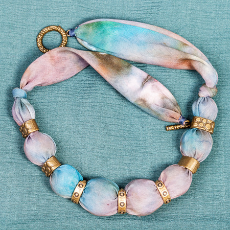 blue background: top view of textile necklace from pink and blue painted silk and bronze beads on green background