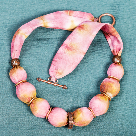 green background pattern: top view of textile necklace from pink and yellow painted silk balls and copper rings on green background