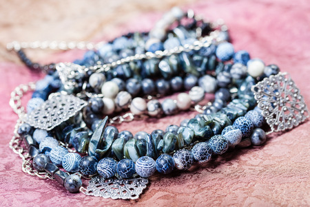 labradorite: tangled gray blue agate necklace from natural gem stones (Dragon Veins Agate, shell, silk jasper, hematite, labradorite beads) on painted textile background