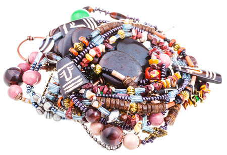 matted: pile of matted necklaces from natural gemstones and carved bone and coconut beads on white textile background Stock Photo