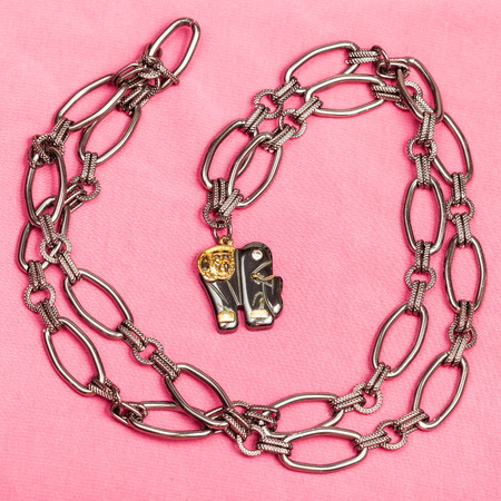 ornamental background: top view of pendant from black chain and elephant figure from carved hematite on pink textile background