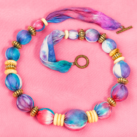 silk background: top view of textile necklace from pink and blue painted silk balls and brass and bone rings on pink background Stock Photo