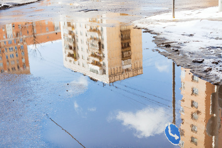 urban houses and sky with clouds reflected in puddle from melting snow on street in sunny spring day