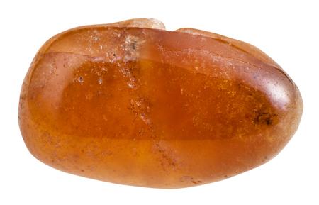 gemology: macro shooting of natural gemstone - tumbled spessartine mineral gem stone isolated on white background