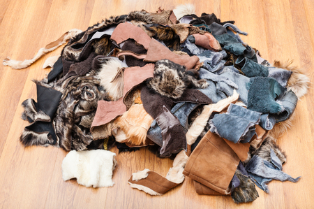 heap of scraps of leather and fur on wooden floor