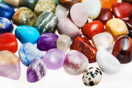 tumbled stones: many tumbled natural mineral gem stones close up on white background Stock Photo